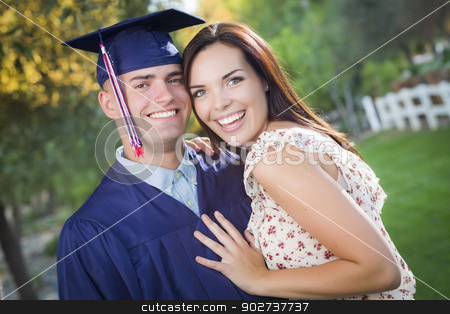 Male Graduate in Cap and Gown and Girl Celebrate stock photo, Happy Male Graduate in Cap and Gown and Pretty Girl Celebrate Outside. by Andy Dean
