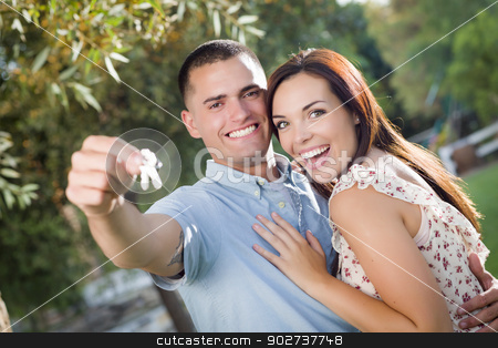 Happy Excited Couple with New House Keys stock photo, Happy Excited Mixed Race Couple with New House Keys Outside. by Andy Dean