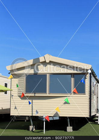 Modern static caravan stock photo, Modern static caravan in trailer park with bunting. by Martin Crowdy
