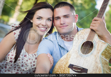 Mixed Race Couple Portrait with Guitar in Park stock photo, Affectionate Mixed Race Couple Portrait with Guitar in the Park. by Andy Dean