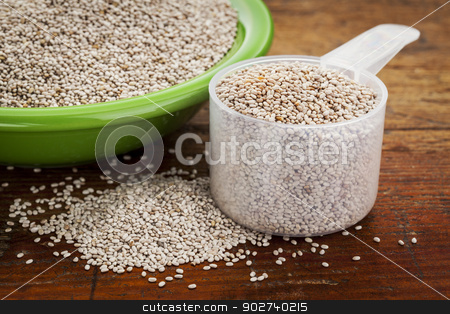 white chia seeds stock photo, white chia seeds -measuring scoop and small side dish bowl against grunge wooden surface by Marek Uliasz