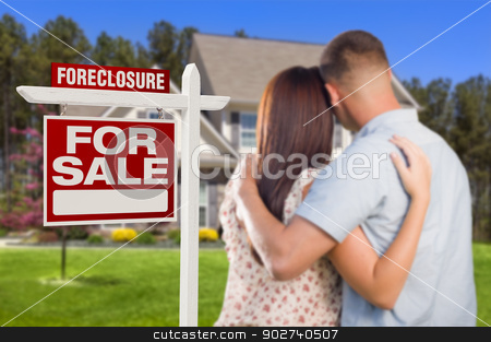 Military Couple Standing in Front of Foreclosure Sign and House stock photo, Military Couple in Front of House and Foreclosure For Sale Real Estate Sign. by Andy Dean