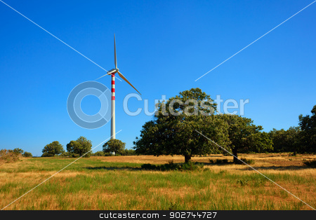 Aeolian energy in Calabria stock photo, Wind turbins producing aeolian energy under blue sky on a green field with chestnut trees in Calabria by Natalia Macheda