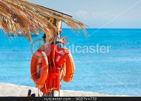 Lifebuoys stock photo, Life-buoys on the beach under palm leaves by Natalia Macheda