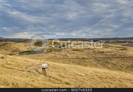 moutain biking in a rolling prairie stock photo, a lonely male biking over rolling prairie illuminated by sunrise at Soapston Prairie Natural Area in northern Colorado near Fort Collins, late summer by Marek Uliasz