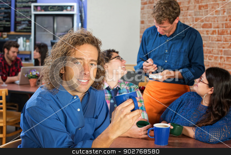 Smiling Man with Coffee Cup stock photo, Smiling Caucasian man with friends and server in cafe by Scott Griessel