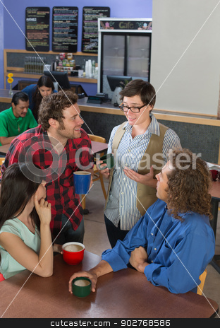 Woman Talking to People in Cafe stock photo, Interested group of people listening to woman in restaurant by Scott Griessel