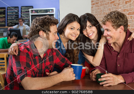 Group of Friends Sitting Together stock photo, Smiling friends sitting next to each other in a cafe by Scott Griessel