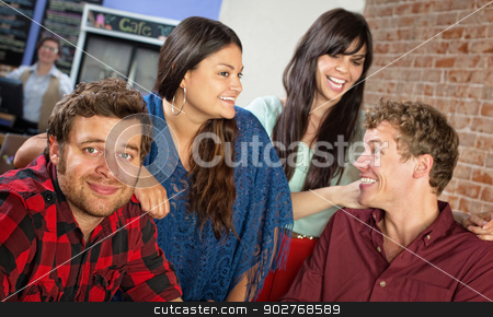 Four Friends in Cafe stock photo, Happy group of cheerful young friends in bistro by Scott Griessel