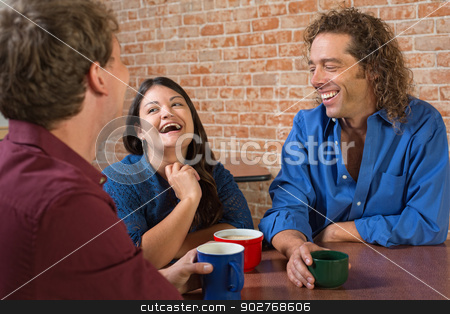 Laughing Coffee House Customers stock photo, Laughing friends with coffee mugs in a restaurant by Scott Griessel
