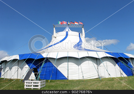 Blue and white big top tent stock photo, Blue and white big top circus tent in field with flags from around World. by Martin Crowdy