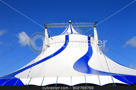 Circus tent  stock photo, Exterior of circus tent with world flags, blue sky background. by Martin Crowdy