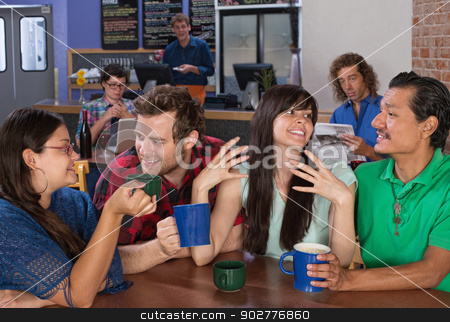 Friends Talking stock photo, Four happy friends talking in a coffee house by Scott Griessel