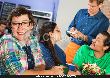 Happy Woman in Cafe stock photo, Happy young woman with eyeglasses in cafe with friends by Scott Griessel