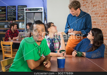 Smiling Man in Cafe stock photo, Smiling Indian man with Caucasian friends in cafe by Scott Griessel