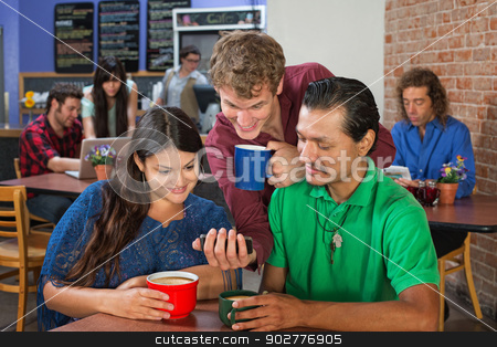 Man Showing Friends Phone stock photo, Young man showing friends phone in cafe by Scott Griessel