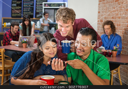 Friends Looking at Phone stock photo, Friends looking a phone in a coffee house by Scott Griessel