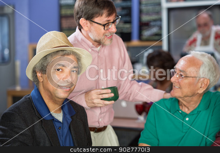 Mature Men Conversing stock photo, Group of mature men conversing in a coffee house by Scott Griessel