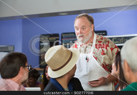 Cafe Employee Helping Customers stock photo, Helpful mature cafe employee talking to customers by Scott Griessel