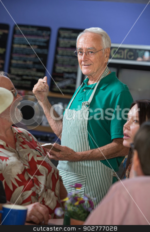 Handsome Host with Patrons stock photo, Handsome senior cafe host helping customers with order by Scott Griessel