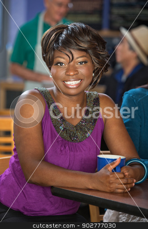 Beautiful Woman in Cafe stock photo, Beautiful smiling woman in cafe with coffee mug by Scott Griessel