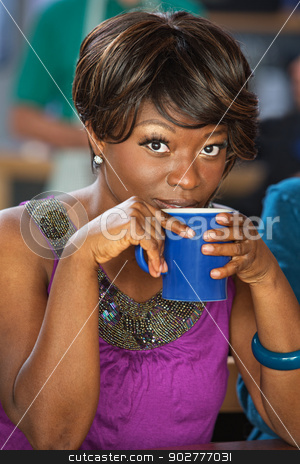 Pretty Woman Sipping Coffee stock photo, Pretty African woman sipping from coffee mug by Scott Griessel