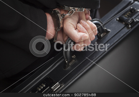 Woman In Handcuffs Carrying Briefcase stock photo, Woman Wearing Handcuffs Carrying Briefcase In Dramatic Lighting. by Andy Dean