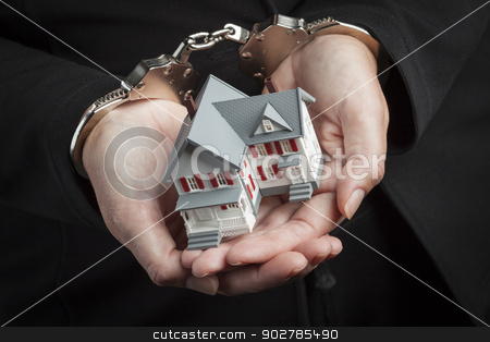 Woman In Handcuffs Holding Small House stock photo, Woman In Handcuffs Holding Small House Against Black. by Andy Dean
