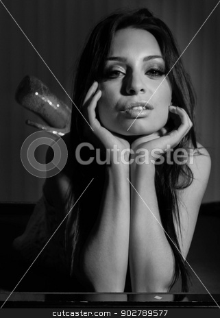 Black White Young Woman stock photo, Young woman lying and holding up her head. by Henrik Lehnerer