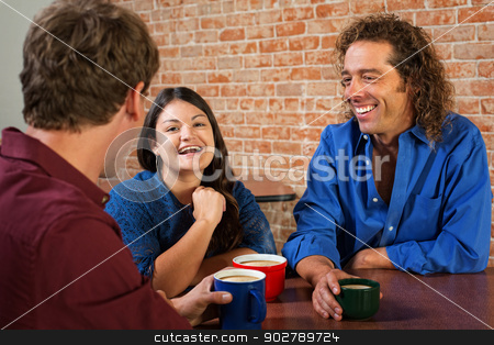 Three Laughing Friends in Cafe stock photo, Three friends laughing and talking in coffee house by Scott Griessel