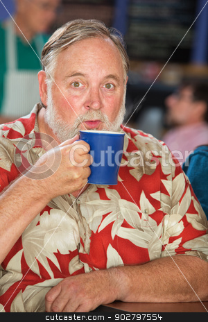 Man Blowing on Coffee Mug stock photo, Man with beard blowing on hot mug by Scott Griessel