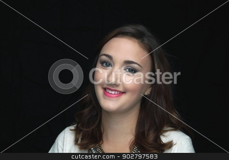 Woman Smiling stock photo, Young woman smiling in front of a black background. by Henrik Lehnerer