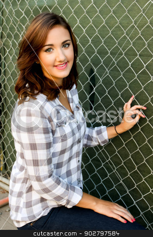 Woman Smiling stock photo, Young woman smiling in front construction fence. by Henrik Lehnerer