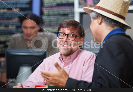 Smiling Man Talking with Friend stock photo, Smiling man talking with friend in a coffee house by Scott Griessel