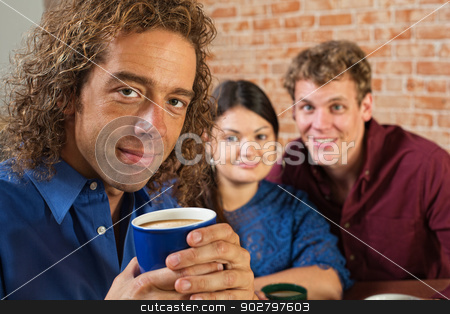 Grinning Man with Coffee Mug stock photo, Grinning man holding coffee mug in bistro by Scott Griessel