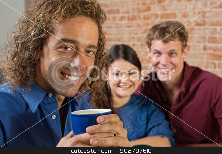 Smiling Man with Coffee stock photo, Smiling man with coffee and friends sitting together by Scott Griessel