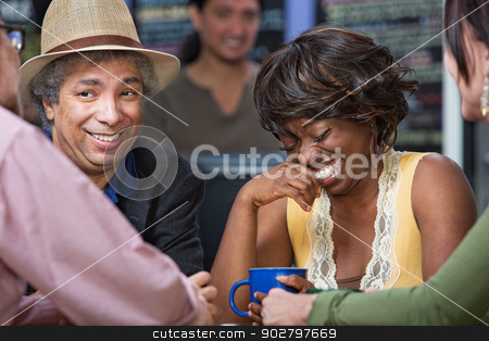 Woman Giggling with Friends stock photo, Diverse group of giggling men and women in coffee house by Scott Griessel
