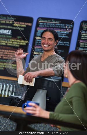 Cute Cafe Worker Pointing at Menu stock photo, Handsome cafe owner showing menu board to female customer by Scott Griessel