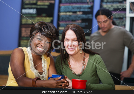 Grinning Friends in Cafe stock photo, Diverse pair of adult friends smiling in restaurant by Scott Griessel