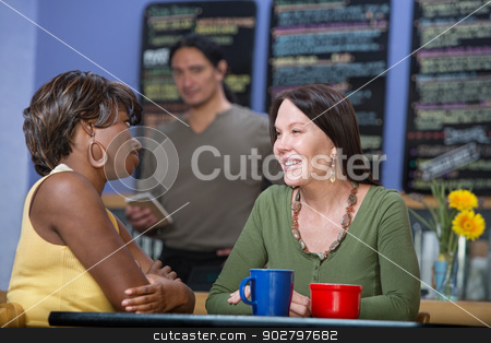 Pretty Women Talking stock photo, Two pretty diverse female cafe customers talking by Scott Griessel