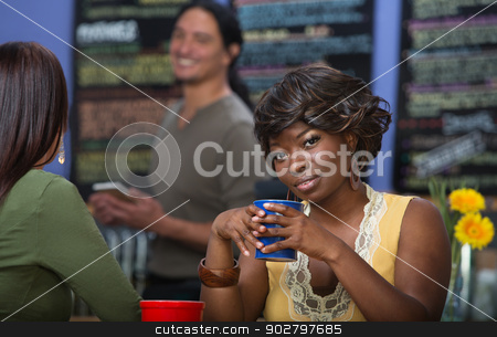 Grinning Woman with Coffee stock photo, Grinning African woman with coffee mug in cafe by Scott Griessel