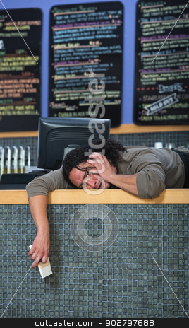 Stressed Out Cafe Owner stock photo, Stressed out worker laying on cafe counter by Scott Griessel