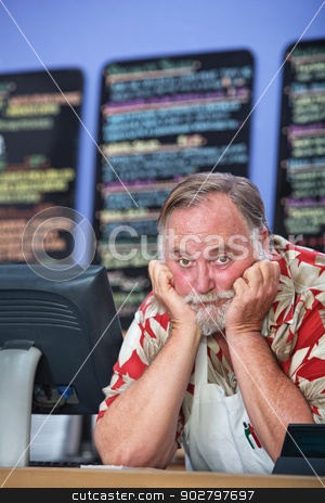 Pouting Restarant Owner stock photo, Pouting man with apron behind restaurant counter by Scott Griessel