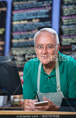 Restaurant Owner Taking Orders stock photo, Senior man with apron behind counter taking orders by Scott Griessel