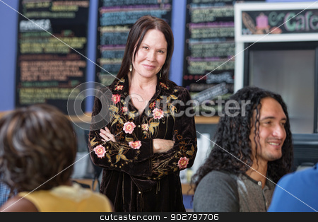 Cute Woman with Folded Arms in Cafe stock photo, Beautiful mature woman standing in coffee house by Scott Griessel