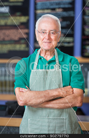 Cheerful Cafe Employee stock photo, Cheerful senior male in apron standing in cafe by Scott Griessel