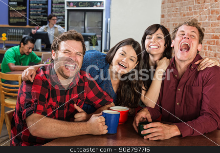 Group of Laughing Friends stock photo, Laughing group of cheerful friends in bistro by Scott Griessel