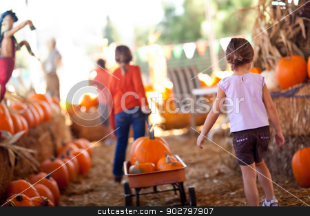Cute Little Girls Pulling Their Pumpkins In A Wagon stock photo, Cute Little Girls Pulling Their Pumpkins In A Wagon At A Pumpkin Patch One Fall Day. by Andy Dean