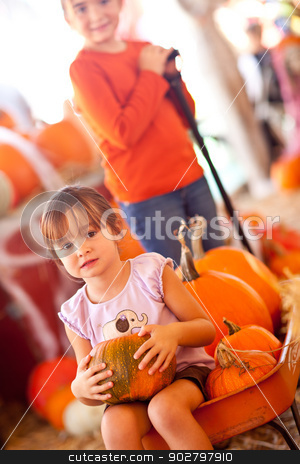Cute Girl Riding Wagon with Her Pumpkin and Sister stock photo, Cute Girl Riding A Wagon with Her Pumpkin and Sister At A Pumpkin Patch One Fall Day. by Andy Dean