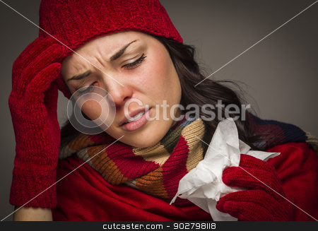 Miserable Mixed Race Woman Blowing Her Sore Nose with Tissue stock photo, Sick Mixed Race Woman Wearing Winter Hat and Gloves Blowing Her Sore Nose with a Tissue. by Andy Dean